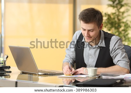 Young businessman working writing notes sitting in a desktop at office - stock photo