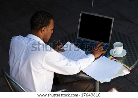 Young Businessman works on a computer outdoors - stock photo