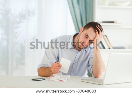Young businessman worried about an invoice - stock photo