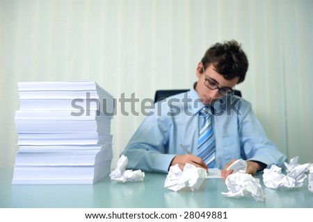 Young businessman writing at a desk with big stack of papers - stock photo
