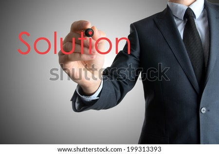 Young businessman writing Solution on white background on grey background - stock photo
