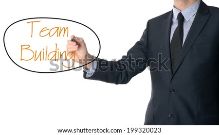 Young businessman writing team building on white background  - stock photo