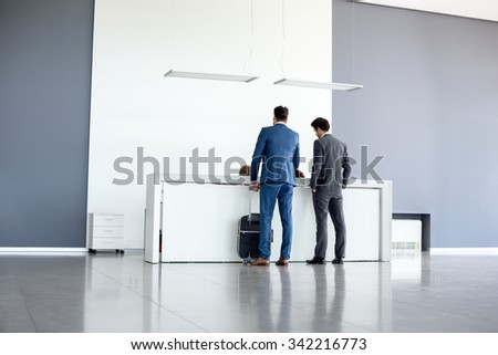 Young businessmen check in at airport reception  - stock photo