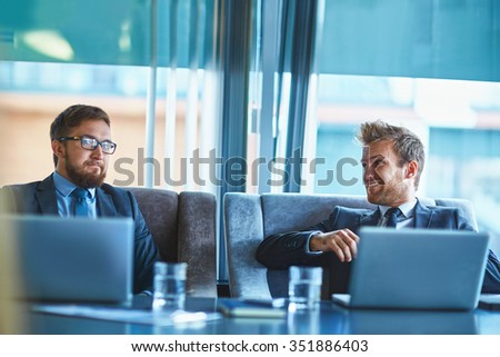 Young businessmen discussing ideas at meeting - stock photo