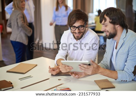 Young businessmen in casual discussing information in digital tablet - stock photo