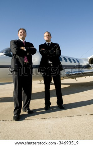 Young businessmen looking to the distance in front of corporate jet - stock photo