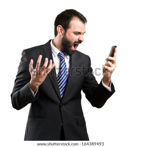 Young businessmen shouting to mobile over isolated background.  - stock photo