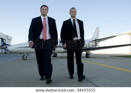 Young businessmen walking away from corporate jet with serious looks. - stock photo
