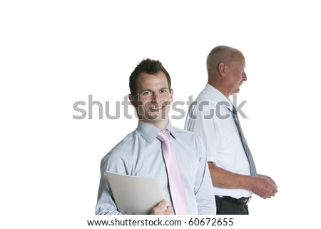 young businessmen with senior businessman in the background - stock photo