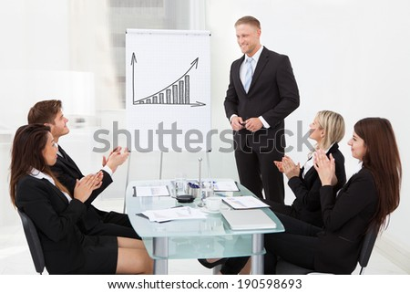 Young businesspeople clapping for colleague after presentation at desk in office - stock photo