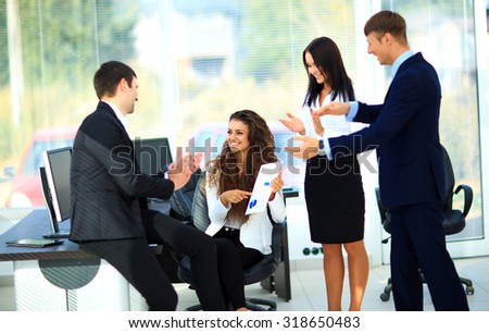 Young businesspeople clapping for female colleague after presentation - stock photo