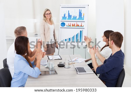 Young businesspeople clapping for female colleague after presentation at desk in office - stock photo