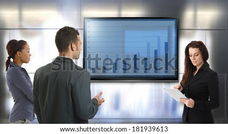 Young businesspeople discussing business results, standing front of big LCD screen. - stock photo