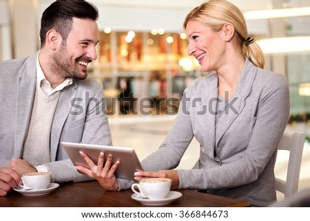 Young businesspeople having a business meeting at coffee shop - stock photo