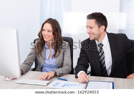 Young Businesspeople Looking At Clipboard Working At Office Desk - stock photo