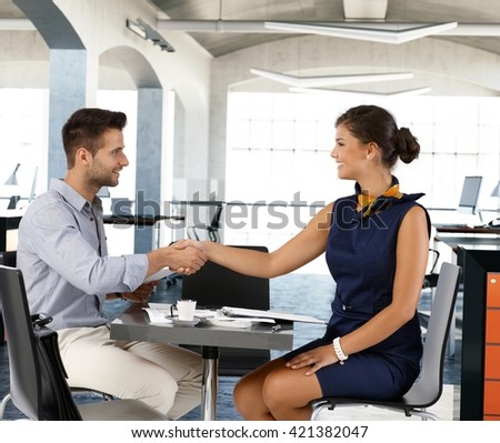 Young businesspeople sitting at coffee table, smiling, shaking hands. Side view. - stock photo
