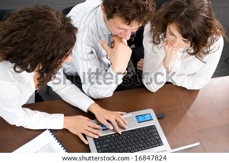 Young businesspeople sitting by table at office, working together on laptop computer. High-angle view. - stock photo
