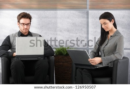 Young businesspeople sitting in office lobby, working on laptop. - stock photo