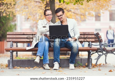 Young businesspeople sitting on a bench working together outdoors - stock photo