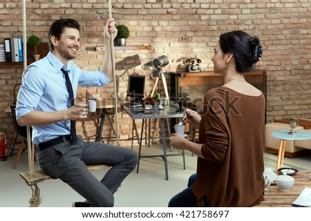 Young businesspeople talking in modern office, businessman sitting on swing, smiling. - stock photo