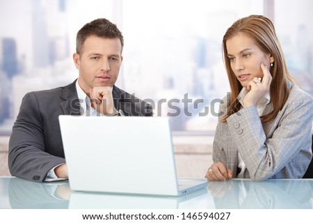 Young businesspeople using laptop, working together in meeting room. - stock photo