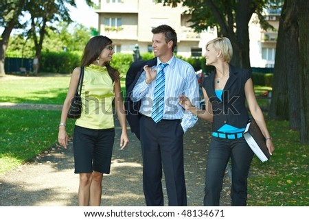 Young businesspeople walking and talking in downtown park. - stock photo