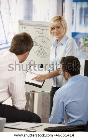 Young businesspeople working together in office, using notebook and whiteboard. - stock photo