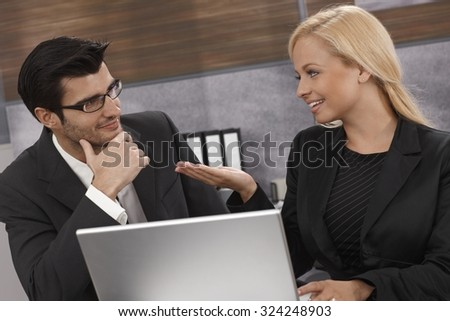 Young businesspeople working together, using laptop computer, talking, smiling. - stock photo