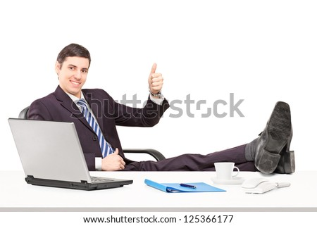 Young businessperson sitting on a chair with his legs up and giving a thumb up isolated on white background - stock photo