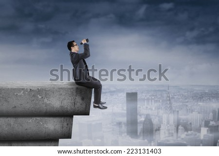 Young businessperson sitting on rooftop and using binocular for looking a solution - stock photo