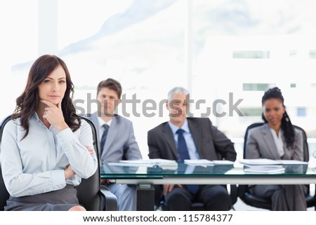 Young businesswoman almost smiling with her hand on her chin in a bright meeting room - stock photo
