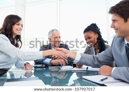 Young businesswoman and a co-worker shaking hands during a meeting - stock photo