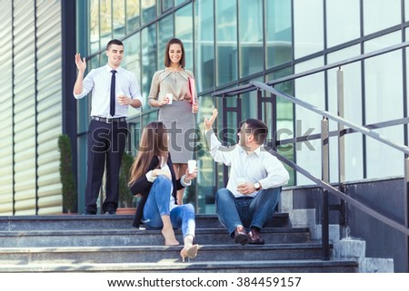 Young businesswoman and businessman sitting on the steps of the office building and drinking coffee while their two colleagues are approaching and greeting them.  - stock photo