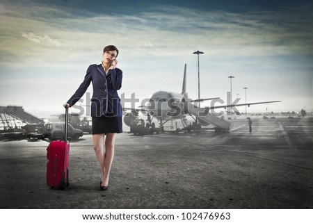 Young businesswoman at the airport holding a trolley case and talking on the mobile phone - stock photo