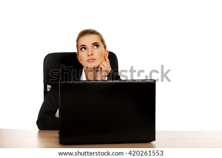 Young businesswoman behind the desk, using laptop - stock photo