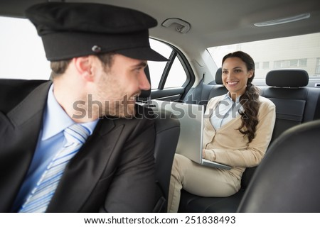 Young businesswoman being chauffeured while working in the car - stock photo