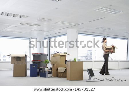 Young businesswoman carrying cardboard box near cartons and equipment in empty office space - stock photo