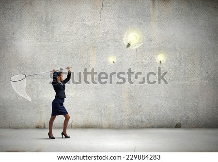 Young businesswoman catching light bulb with hoop - stock photo