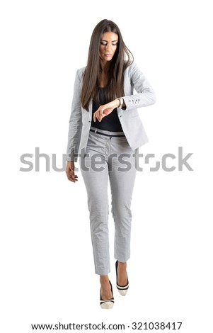 Young businesswoman checking hand watch walking forward in the rush. Full body length portrait isolated over white studio background.  - stock photo