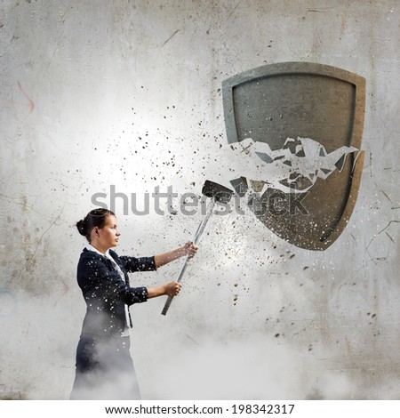 Young businesswoman crashing stone shield with hammer - stock photo