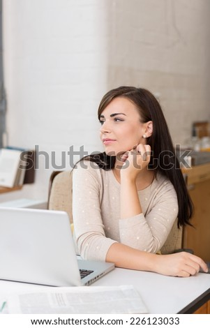 Young businesswoman daydreaming in the office sitting at her desk staring off to the side with a dreamy expression - stock photo