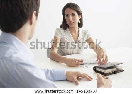 Young businesswoman discussing with male colleague at desk in office - stock photo