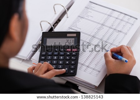 Young Businesswoman Doing Calculations In The Office - stock photo