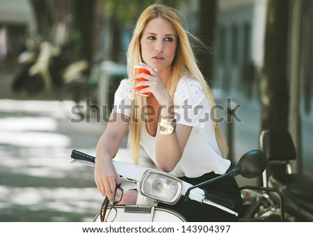 Young businesswoman drinking a coffee on a italian scooter. / Blonde woman standing on the street. - stock photo