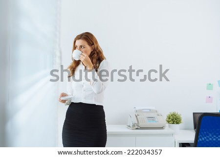 Young businesswoman drinking coffee and looking through window in office - stock photo