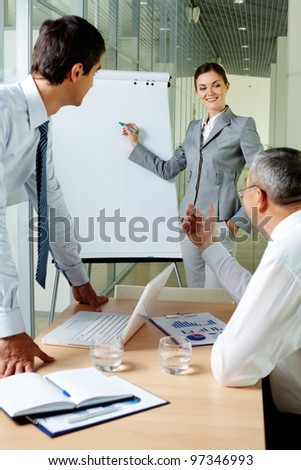 Young businesswoman explaining her ideas on whiteboard at meeting - stock photo