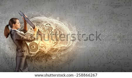 Young businesswoman fixing gears mechanism with wrench - stock photo