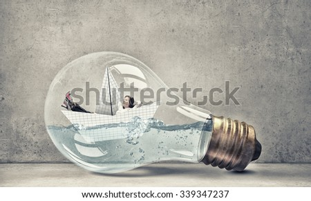 Young businesswoman floating on paper boat inside of light bulb - stock photo