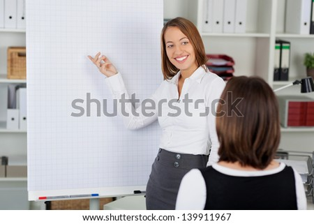 Young businesswoman giving presentation to female coworker in office - stock photo