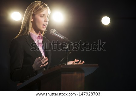 Young businesswoman giving speech at podium in auditorium - stock photo